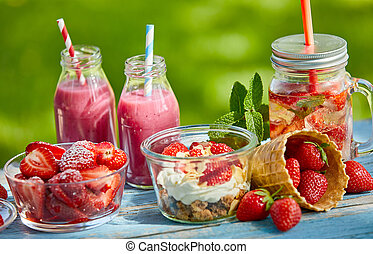 Fresh, sweet, healthy summer berry smoothie bowls and juices on a bright outdoor table setting.