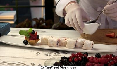 Sweet sushi rolls on table. Chef holding sauce bowl. Best...