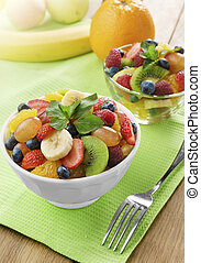 Sweet tasty fruit salad in the bowl on the wooden table