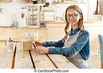 Sweet teenage girl familiarizing herself with a menu - ...