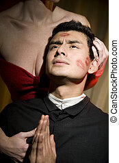 Tempted priest clasping his hands in prayer
