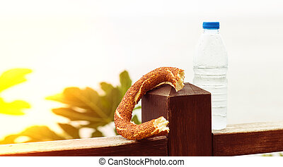 Sweet Turkish roll - simit and a bottle of water on the background of the sea, the concept of health