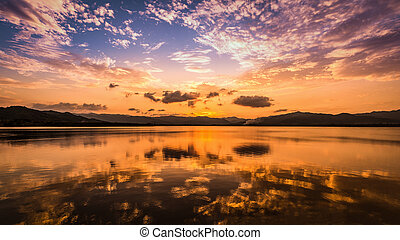 Sweet twilight sunset sky and clouds reflect on flat water surface