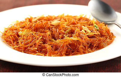 Sweet vermicelli on a white plate with spoon