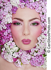 Portrait of beautiful green-eyed girl with fancy makeup and flowers of sweet williams around her face