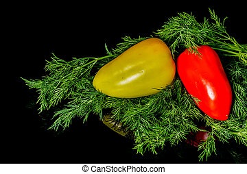 Sweet yellow and red peppers with dill isolated on a black background