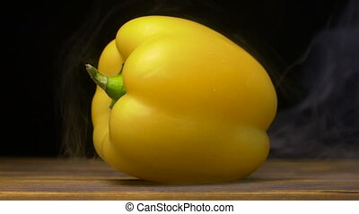 sweet yellow bell pepper or capsicum is on the table in...