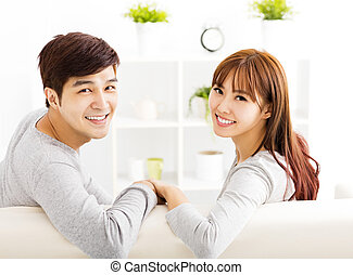 sweet young couple sitting in sofa
