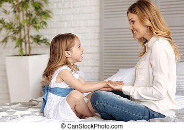 Sweet young mother holding hands of her daughter