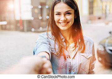 Sweet young woman holding the hand of photographer