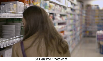 Sweet young woman walking on the supermarket and choosing products