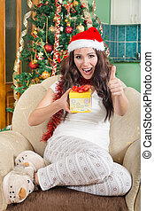 Sweet young woman with Christmas gift showing thumbs up