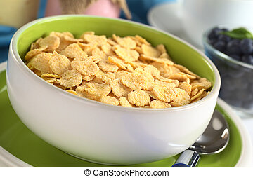 Sweetened corn flakes with yogurt, coffee cup and blueberries in the back (Selective Focus, Focus one third into the bowl)