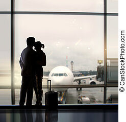 sweethearts in airport - silhouette of pair of lovers near...