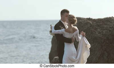 Sweethearts newlyweds dancing on the seaside near cliffs