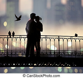 sweethearts - silhouette of bridge and pair of lovers on...
