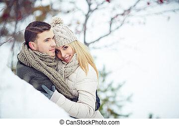 Sweethearts - Smiling girl looking at camera while embracing...