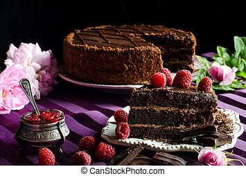 A piece of chocolate cake with raspberries. Vintage silver jar with a spoon. The celebration desserts. Summer dessert. Purple tablecloth. Fresh berries. Tea rose.
