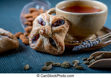 Sweet cookies and a cup of red tea with seasonings and lavender on blue wooden table