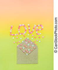 Sweets sugar candy hearts fly out of craft paper envelope and create word Love on the bright gradient background . Valentine day. love diversity concept. Gift, message for lover. Space for text.