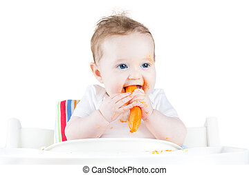 Swet baby eating her first solid food in a white chair, isolated