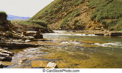 Swift mountain river flows through a highland valley in...