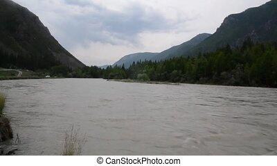Swift water flow in mountain river, rocks along the river...