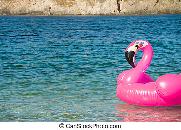 swim ring in the shape of a pink flamingo on the water near the beach, water background. Fancy swim ring. Summer holiday. Relax time