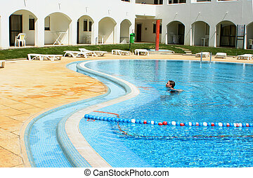 swimmer - boy wades in the pool at resort