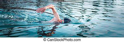 Swimmer breathing during swimming crawl. Panorama