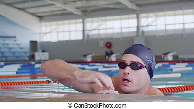 Swimmer coming out of water and looking at camera - Front ...