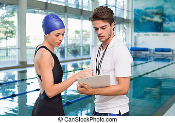 Swimmer discussing times with her coach by the pool at the ...