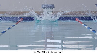 Front view of Caucasian male swimmer at swimming pool, diving from a starting block during a swimming competition and plunging into the water, in slow motion