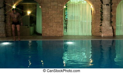 Swimmer in pool - Energetic guy diving into water, swimming...