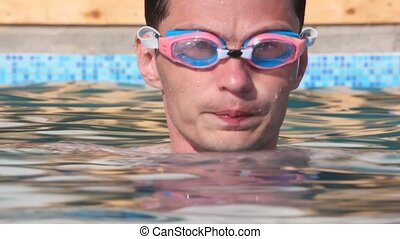 swimmer men with goggles diving in waterpool with blue water