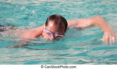 swimmer men with goggles swimming in waterpool with blue water