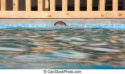 swimmer men with goggles swimming in waterpool with blue water to camera