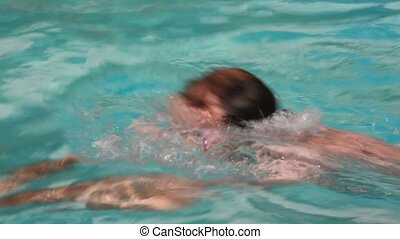 swimmer men with goggles swimming in open-air waterpool with blue water