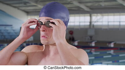 Side view of Caucasian male swimmer at swimming pool, putting on his pool goggles in preparation for a race, wearing swimming cap, in slow motion