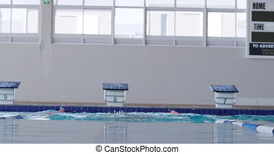 Front view of Caucasian male swimmer at a swimming pool, racing in a lane during a swimming competition, swimming the butterfly stroke, in slow motion