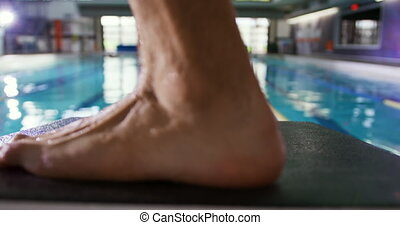 Close up of feet of a young Caucasian male swimmer standing on a starting block by a swimming pool during training