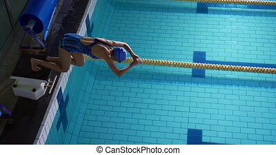 Side view of a young Caucasian female swimmer training in a swimming pool, jumping into water