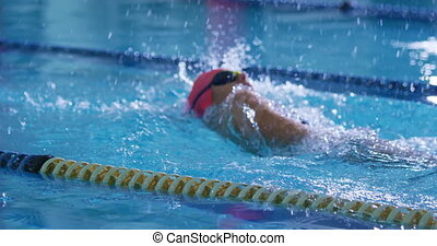 Side view of a young Caucasian female swimmer training in a swimming pool, backstroke