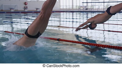 Swimmers diving into the pool - Close up of multi-ethnic ...