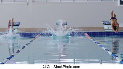 Swimmers diving into the pool - Front view of multi-ethnic ...