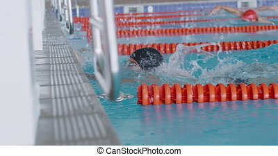 Side view of multi-ethnic group of male swimmers at swimming pool, racing each other in lanes, swimming crawl, holding starting block, one of them raising his arm in victory, in slow motion