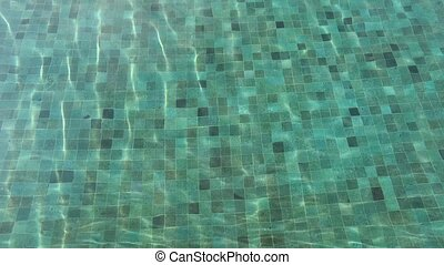 swimming and spa concept - tiled bottom in water pool