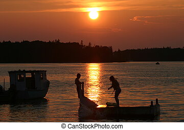 Swimming at Sunset - A couple of kids on a floating dock in...
