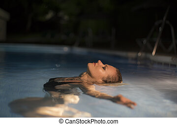 swimming, beautiful blond woman in a swimsuit in a pool at night