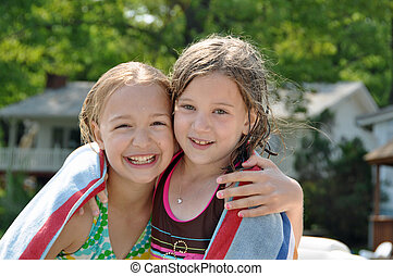 two girls hug while drying off after swimming